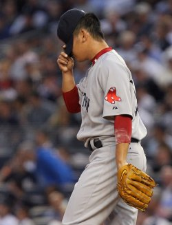 Boston Red Sox starting pitcher Daisuke Matsuzaka grabs his cap between pitches at Yankee Stadium in New York