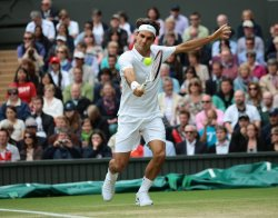 Roger Federer returns on the seventh day at Wimbledon Tennis Championships
