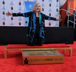 Kim Novak places hands and footprints in wet cement at Grauman's in Los Angeles