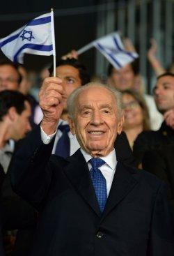 File Photo of Israeli Leader Shimon Peres Waving An Israeli Flag