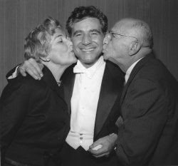 Leonard Bernstein is kissed by his parents after his first concert as conductor of the N.Y. Philharmonic Orchestra