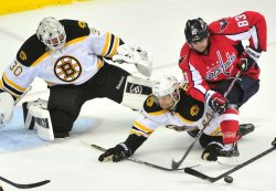 Capitals Jay Beagle is stopped by Bruins Dennis Seidenberg and goalie Tim Thomas in Washington