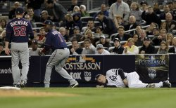 New York Yankees first base coach Mick Kelleher lies on the ground after being hit by a ball in Game 3 of the 2010 ALDS at Yankee Stadium in New York