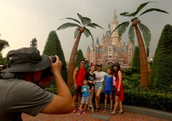 Chinese take group photos in front of the Disney castle in Shanghai Disneyland, China