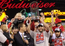 Cardinals Lance Berkman holds up the Commissioner's Trophy after winning the 2011 World Series in St. Louis