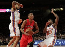 Toronto Raptors DeMar DeRozan drives the ball between New York Knicks Tyson Chandler and Toney Douglas at Madison Square Garden in New York