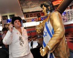 An Israeli Elvis impersonator sings beside a statue of Elvis draped with an Israeli flag outside Jerusalem