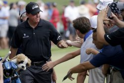 Phil Mickelson bumps fists with fans at the PGA