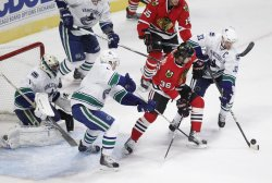 Blackhawks Bolland and Canucks Sedin, Ehrhoff fight for puck in Chicago