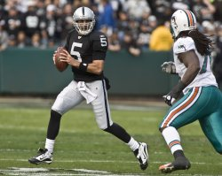 Raiders QB Bruce Gradkowski rolls out to pass under pressure from Dolphins Tony McDaniel in Oakland, California