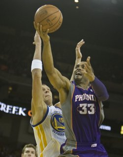 Phoenix Suns Grant Hill lays up a shot past Golden State Warriors Andris Biedrins in Oakland, California