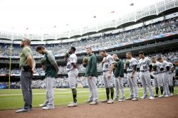 Athletics players stand on the field at Yankee Stadium