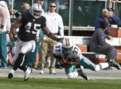 Dolphins Yeremiah Bell picks off a Bruce Gradkowski pass in Oakland, California