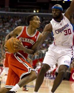 Milwaukee Bucks' Brandon Jennings drives by Los Angeles Clippers' Reggie Evans in Los Angeles