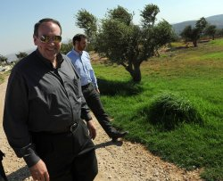 Former U.S. Presidential candidate Mike Huckabee walks by olive trees in the Givot Olam settlement outpost in the West Bank
