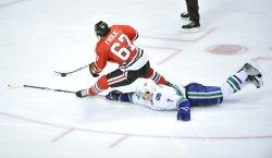 Canucks Hamhuis takes down Blackhawks Frolik in Chicago
