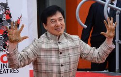 Jackie Chan places hands and footprints in wet cement at TCL Chinese Theatre in Los Angeles