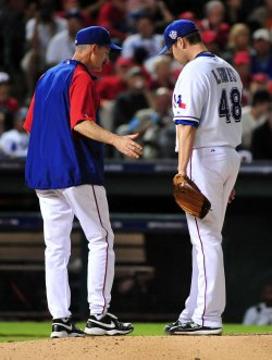 Rangers' pitching coach Mike Maddux talks to pitcher Darren O'Day in game 3 of the World Series in Texas