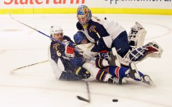 Atlanta Thrashers Ron Hainsey (6) takes down New York Rangers Chris Drury and the both slide into goalie Johan Hedberg in the second period at Madison Square Garden