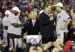 New England Patriots Vince Wilfork, Owner Robert Kraft, Jim Nantz and Tom Brady stand with the Lamar Hunt Trophy in the AFC Championship Game at Gillette Stadium in Massachusetts
