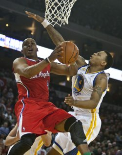 Clippers Randy Foye drives on Warriors Brandon Rush in Oakland, California