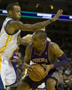 Phoenix Suns Grant Hill ducks under the inked arm of Golden State Warriors Monta Ellis in Oakland, California
