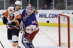 New York Islanders Matt Moulson and New York Rangers Henrik Lundqvist (30) watch a loose puck at Madison Square Garden in New York