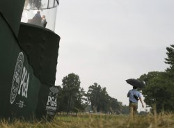 A fan walks with an umbrella at the PGA