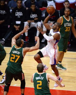 Clippers guard Chris Paul (R) shoots over Jazz center Rudy Gobert in Los Angeles