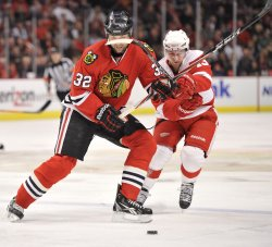 Blackhawks Scott and Red Wings Datsyuk go for puck in Chicago