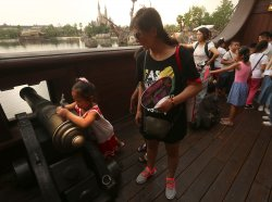 A young Chinese girl 'fires' a canon on display in Shanghai Disneyland, China