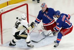 Pittsburgh Penguins Matt Cooke gets a puck by New York Rangers Martin Biron and Marian Gaborik at Madison Square Garden in New York