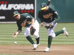 A's Cliff Pennington bare hands a grounder in Oakland, California