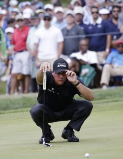 Phil Mickelson lines up a putt on the 4th hole at the PGA