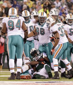 Miami Dolphins Randy Starks, Paul Soliai (96), and Yeremiah Bell surround New York Jets LaDainian Tomlinson at New Meadowlands Stadium in New Jersey