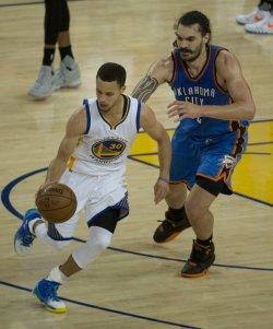 Warriors Stephen Curry dribbles around Thunder's Steven Adams