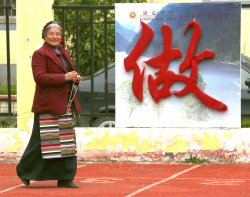 A Tibetan mother watches students exercise at a middle school in Ganzi Prefecture