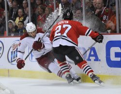 Phoenix Coyotes forward Taylor Pyatt and Chicago Blackhawks defenseman Johnny Oduya go for the puck in Chicago