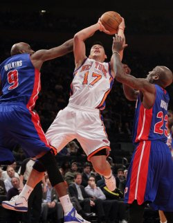 New York Knicks Jeremy Lin shoots the ball between Detroit Pistons Damien Wilkins and Walker Russell at Madison Square Garden in New York