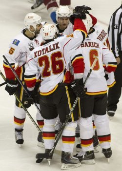 Flames Bourque is Mobbed After Scoring Winning Goal Against the Avalanche in Denver