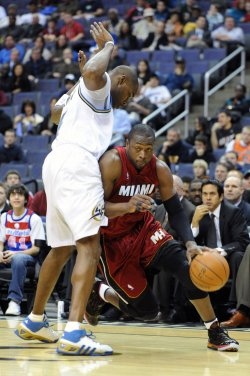 Heat Wade drives toward basket against Wizards Jamison in Washington