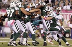 Miami Dolphins Daniel Thomas is held up by New York Jets David Harris at MetLife Stadium in New Jersey