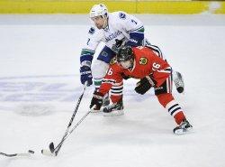 Canucks Hamhuis and Blackhawks Kruger go for puck in Chicago