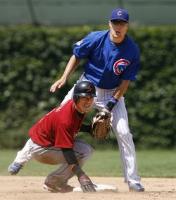 Chicago Cubs second baseman Jeff Baker (R) and Houston Astros' Kazuo Matsui look back to first base