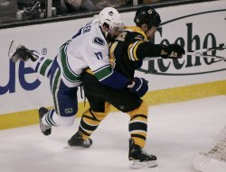 Canucks Kesler holds Bruins Ference in game 6 of the NHL Stanley Cup Finals in Boston, MA.
