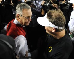 Ohio State head coach Jim Tressel shakes hands with Oregon head coach Chip Kelly (R) at the Rose Bowl in Pasadena, California