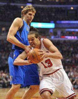 Bulls' Noah drives on Mavericks' Nowitzki in Chicago