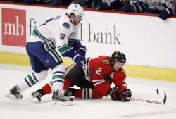 Blackhawks Keith and Canucks Bernier go for puck in Chicago