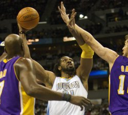 Nuggets Nene Shoots between Lakers Gasol and Odom at the Pepsi Center in Denver
