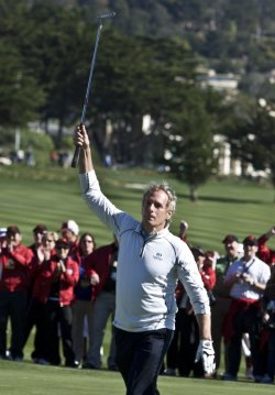 Singer Michael Bolton celebrates sinking a putt at Pebble Beach, California